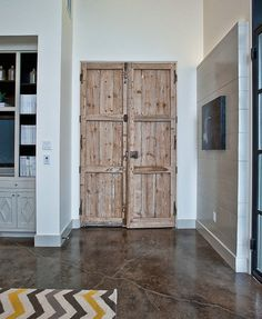 Wooden pantry doors, concrete floor, and modern patterned rug. Cat Mountain Residence modern media room