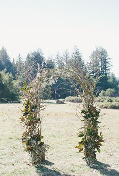 Brides.com: 30 Amazing Ceremony Altars. A rustic iron arch covered in greenery and branches.