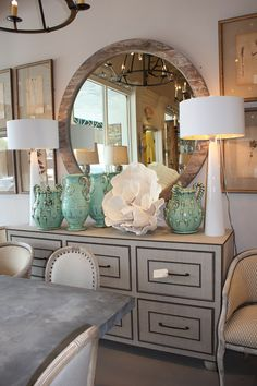 Giant round mirror w/worn Finnish, fabric and nailhead trim dresser. Awesome.