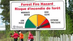 Fire rangers walk past a forest fire hazard sign as they walk to a helicopter to battle a forest fire just a few kilometres west of Timmins, Ont., on Saturday, May 26, 2012. (Nathan Denette / THE CANADIAN PRESS)