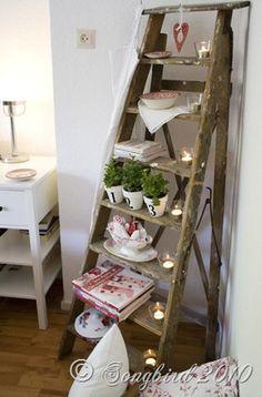 I love this old ladder...turned potted herb holder, candle holder, dish holder, and apron holder.