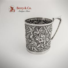 "American sterling silver mug with ornate repousse floral and foliate decorations by Justis & Armiger of Baltimore, Maryland. c.1880. Inscribed ""Mary W. Ward from her father J. Harry Ward"" in ornate period script on the bottom of the mug."