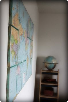 Buy some canvases and modge podge a world map to create a beautiful display.