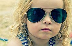 Enfant avec lunettes de soleil d'adulte