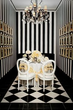 carrelage damier noir et blanc, table à manger blanche avec chaises, murs rayés