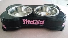 Double dog bowl - bone shaped with rubber feet. Each stainless steel bowl is removable and dishwasher safe. The Black dog-bone shaped container