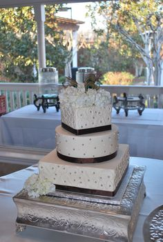 Wedding Cake with scroll work, colored sugar pearls, ribbon and peacock feathers. www.callingallcakes.com