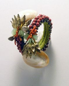 Haskell Seashells Wrap Bracelet USA, circa 1940 Spring wire covered with green silk thread, pate de verre beads imitating coral and jade, each end of bracelet comprised of gold plated leaf forms, coral twig forms, one small shell and one large shell with appearance of mother-of-pearl