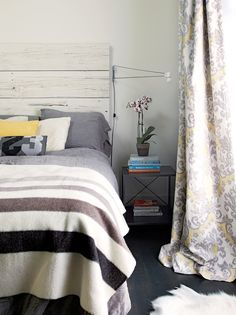 Fabulous bedroom with whitewashed plank headboard paired with gray linen washed linen bedding and striped flannel blanket next to industrial nightstand filled with books and orchid as well as yellow and gray curtains.