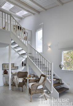 Salón doble altura con escalera de madera.