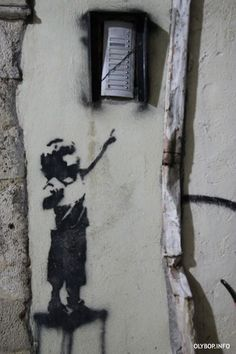 street art by Banksy. Child reaching for doorbell.