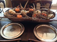 Close up of autumnal dining centerpiece using dough bowl, pine cones, Spanish miss, mini pumpkins, deer antlers and bittersweet.  No need to remove during dinner because provides viewing ease of your dinner companions.  Great rustic look that works well with refined accessories.