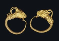 A PAIR OF GREEK GOLD GOAT HEAD EARRINGS  HELLENISTIC PERIOD, CIRCA 3RD CENTURY B.C.  Each with a hoop of spiralling plain wire tapering to plain wire that hooks through a loop on the underside of the goat head terminal, with a collar of wire tongues joined to the neck, the ridged goat horns curving over the separately-made elongated ears, the fleece incised around the jaw