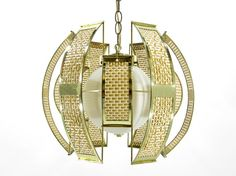 Mid century, Hollywood Regency pendant light in shiny brass with natural woven cane panels. Layered panels surround a white, frosted glass globe. Includes a matching brass chain.    In excellent vintage condition, with minimal signs of wear. In working condition, with original wiring. This lamp may be plugged into a wall outlet, or fitted for hard wiring.
