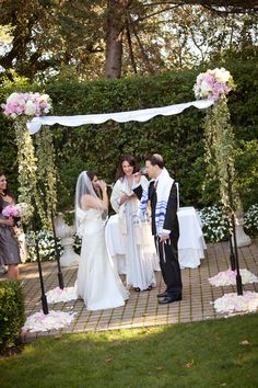 Ceremony Decor:  A Jewish ceremony huppah with fabric draping, floral pieces of Roses and Hydrangea in pinks and whites, with long trailing accents of variegated Wedding Ivy, and mounds of pink and white Rose petals around huppah bases.  By Heather Murdock of The Blue Orchid (image by Dorothy Hatchel Photography)