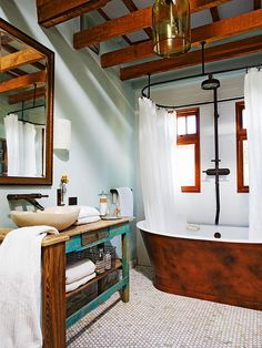 Wooden ceiling beams and a tub gives this cottage style bathroom rustic charm.