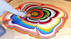 "Holton Rower creates ""pour paintings"" by continuously pouring paint onto plywood."