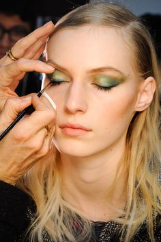 fall 2012 jason wu  Use MAC Powerpoint Eye Pencil in Tealo to create a base for Eye Kohl in Minted, a light green, layered through the crease. To add texture and dimension, blend MAC Eyeshadow in Club and its Pigment in Kelly Green outward toward the temple before tracing the lash line with its Eye Kohl in Blooz, a dark blue, and a black cream liner to extend the elongated shape of the pigments in cat-eye shape. MAC Haute and Naughty Mascara amplified top lashes only, while lips were left…