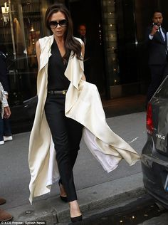 Flowy: The wind whipped up Victoria's coat as she left the British Embassy, showing off her black cigarette pants and blouse