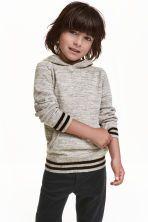 Pull à capuche en coton: Pull en maille fine et souple de coton. Modèle avec capuche doublée. Finition bord-côte à la base et en bas des longues manches raglan.