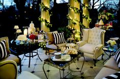 From Nellhills.com blog, ring in the new year on th back porch. Champagne bottles on ice in a silver punch bowl.  beautiful 3-tier silver dessert tray. Unexpected wingback chair upholstered in vinyl for easy care in the elements. Very classy.
