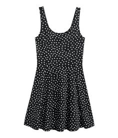 Black/dotted. Short, sleeveless dress in thick jersey. Low-cut neckline at back, seam at waist, and flared skirt.