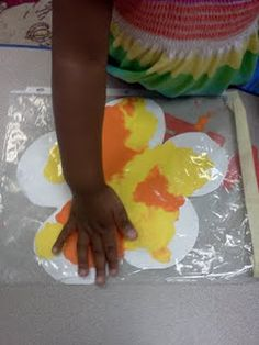 Mess free art. Cut out flower shapes. pick out 2 colors. Tape the top closed, and let the kids smush the paint around.