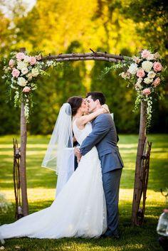 Arco retangular feito de madeira natural e decorado com arranjos florais