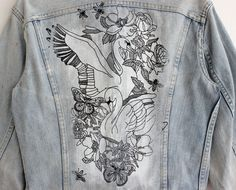 Vintage Lee Riders denim jacket, customized with tattoo style original artwork at the back: Swans, bees, flowers and butterflies are gathered together in a grungy scene, made with hand painting and silk screen print technique.  This unique upcycled jacket is part of a limited edition collection we made with the illustrator Liora Zemelman: The jackets are vintage items and the paintings are hand made. There are only 10 numbered jackets in this collection and each of them is one of a kind.  We…