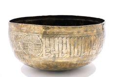 GRAND BASSIN MAMELUKE DU XVe SIÈCLE en laiton, à décor gravé d'un large bandeau en thuluth ornemental alternant avec du kufi fleuri et noué et avec quatre médaillons également inscrits en thuluth et oirnés de fleurons. La titulature se lit : (al)-maqarr al-ashrafi al ashrafi al- âlimi al- amili al- âdili (…) al- âlimi al-mâliki al- âmili al- amili = Sa noble excellence, excellence, le Savant, le Pratiquant, le Juste, le Savant, le Seigneur, l'Eminent, le Savant...