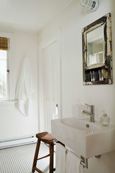 Rustic bathroom design with glossy white sink, reclaimed wood mirror, bamboo roman shade, beadboard and wood stool.