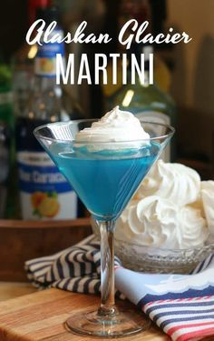 This delicious Alaskan Glacier Martini Recipe is made up of vodka gin light rum blue curacao sweet n sours mixer and topped off with a splash of lemon-lime soda. But the icing on the cake is the sweet and airy meringue cookie glacier floating on the top! Martini Recipes, Alcohol Drink Recipes, Cocktail Recipes, Blue Martini Recipe, Easy Alcoholic Drinks, Vodka Drinks, Martinis, Beverages, Martini Bar