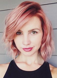 Wavy Pink Bob This style is cute, to say the least. The wavy bob can often be viewed as such, but with the addition of the rose gold hair color, the pink just makes it that much more fun and, well, cute! By darkening the color at the roots, you will also ensure longevity with your look, but will also add fluidity by giving it motion. The color, as seen here, can be worn with black quite well, but playing around pairing it with other hair colors could prove to be a fabulous decision.