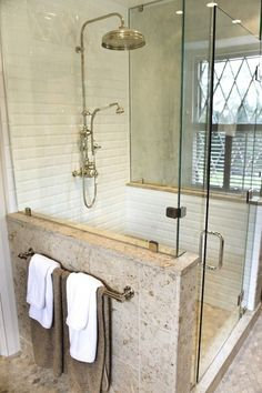 Seamless glass shower with glossy white beveled subway tiles shower surround, rain shower head, stone bench and Napolina Limestone tiles shower floor in diamond pattern.