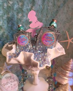 Mermaid Bubbles in a darling bottle! May all our trubbles turn into bubbles! These darling Swoon Moon Apothecary bottles are filled with faux bubbles made of Czech Republic glass with an Aurora Borealis finish. The stainless steel chain is embellished with frosted violet glass starfish, faceted aquamarine glass beads and frosted teal Czech beads. The entirety of the bottle and chain have a luxurious weight and fanciful feel.