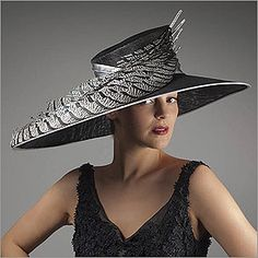 • Dressage  • Design by Vivien Sheriff   • Sinamay Base, Silk Sash, Lady Amhurst Pheasant Tails, Wire Wrapped Quills, Swarovski Crystals  • Colors: Black and White  • Size: Fits Most  • Handmade in the UK  • Vivien Sheriff is a renowned designer from England. Her hats have fitted the heads of British royals and are now available to you through HATagories.