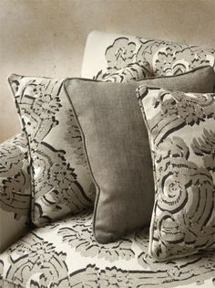 Lizzo -  Samarkanda Fabric Collection - Three dimensional effect pattern with grey swirls and flowers shaded with black, on a white sofa and cushions, with a plain grey cushion