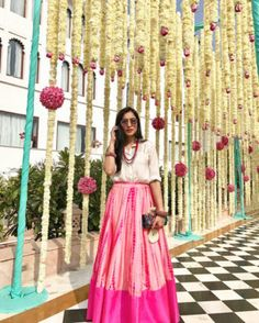 Light Lehengas - Pink Plain Ombre Lehenga teamed with a White Shirt | WedMeGood | Light Outfit with Floral Hanging Decor  #wedmegood #indianbride #indianwedding #lehenga #lightlehenga #pink #ombre #whiteshirt #unique