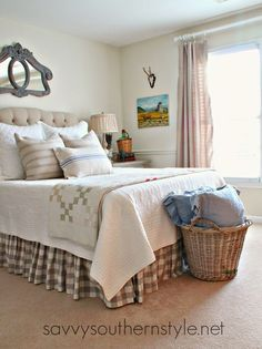 French country style guest room, vintage quilt, vintage French ticking pillows, buffalo checked bed skirt, vintage Belgium bulb basket, upholstered headboard, linen