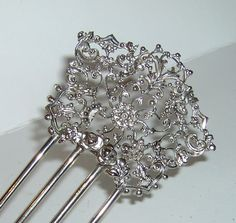"Vintage silver lace hair comb.    This is exqusite and very, very feminine.  All silver lace with delicate turned in sides.  It shows a little age on the teeth but that is normal since this was probably made in the 1850s or 60s.  This is altogether a  wonderful item for the collector.  Measurement:   5"" x 3""  Condition:  Very Good"