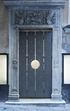 italian studio gosplan inserts a modern perforated metal gate into a fifteenth century marble doorway. fashion boutique in genoa.