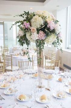 Elegant table centerpiece white and pink flowers with greenery. Find your florist at WeddingWire!
