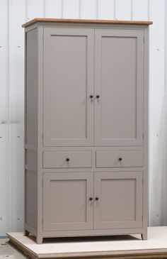 Shaker style freestanding larder cupboard handpainted in Farrow & Ball Estate Egshell - 'Charleston Gray'. Tulip wood carcass with painted birch ply panels and oak faced birch ply shelves. Dovetailed oak drawers on high quality soft close runners. Oak spice racks. High quality solid brass hinges and adjustable brass shelf supports. Solid oak cornice and walnut knobs.