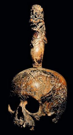 DAYAK CARVED: HEAD HUNTING HUMAN TROPHY  SKULL WITH CARVED WOODEN FIGURE  CARVED HUMAN BONE AND WOOD  THE DAYAK TRIBE, FROM BORNEO ISLAND  INDONESIA, CARVE DESIGNS INTO THE SKULLS  OF THEIR HEADHUNTED VICTIMS AND INSERT WOODEN FIGURES.