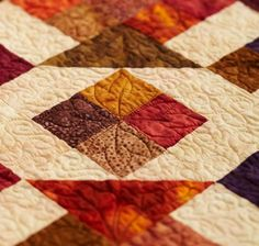 In each block, Sandy Pluff machine-quilted leaves in the medium and dark batik pieces.