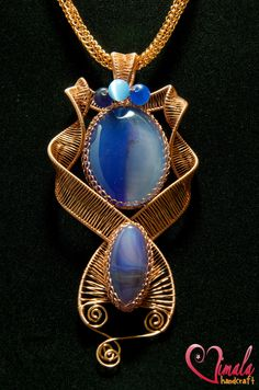 wire wrapped jewelry - I can see an orchid where the large blue stone is and maybe a bud where the smaller stone is.