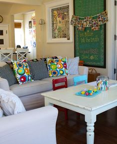 I love family-friendly spaces  like this....the chalkboard, the coffee table with chairs for the wee ones!  <3