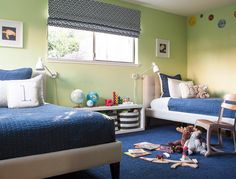 Shared blue and green boys' bedroom boasts beige tufted twin beds dressed in navy blue and white bedding and positioned under framed blue and yellow prints hung from a wall painted in Benjamin Moore Potpourri Green.