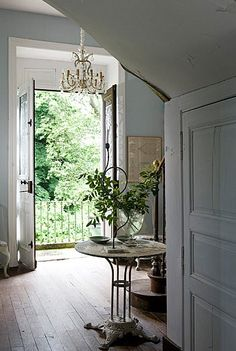 double-door entryway; complete with blue walls, gold and glass chandelier, and wood floors