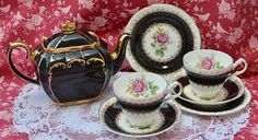 Vintage bone china tea set for two, made by English china company Harrowby and well known teapot maker Sadler, likely manufacture date 1960s. The set consists of full size teapot, tea cups, saucers and tea plates- two of each and a milk jug and sugar bowl. The Harrowby china is predominantly black with a picture of a pink rose on the inside of the cups and in the centre of the plates and saucers. The china is further enhanced with gilding to the rims of the pieces, feet and handles of cups…